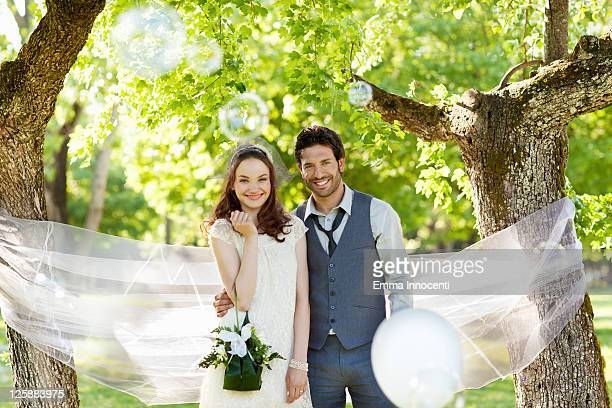 newlywed, trees, bubbles, tulle, toothy smile