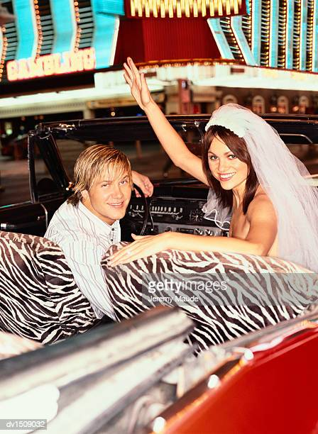 Newlywed Young Couple Riding in a Convertible Car in a Street in Las Vegas, USA