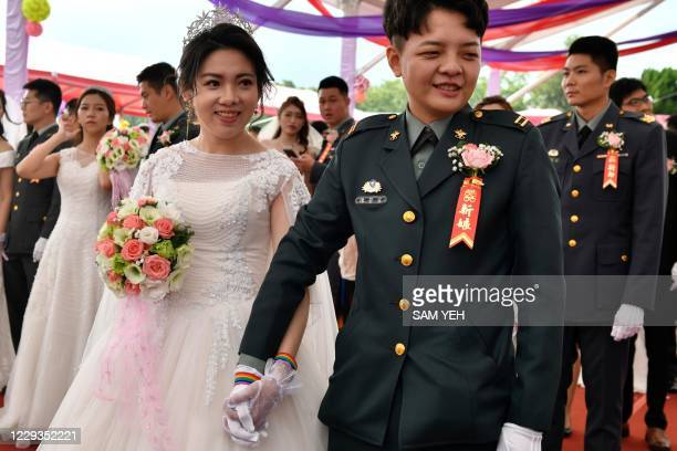 Newly-wedded same-sex couple Chen Ying-hsuan and Li Li-chen take part in a mass wedding at Taiwan's Army Command Headquarters in Taoyuan on October...