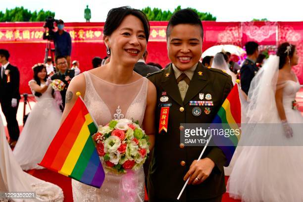 Newly-wedded same-sex couple Yi Wang and Yumi Meng pose for a photograph during a mass wedding at Taiwan's Army Command Headquarters in Taoyuan on...
