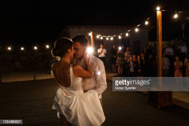 newlyweds are kissing at the dancing stage - wedding stock pictures, royalty-free photos & images