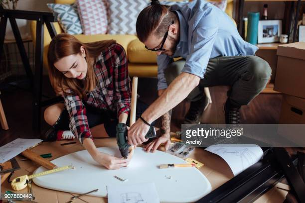 Newlyweds assembling new coffee table for their home