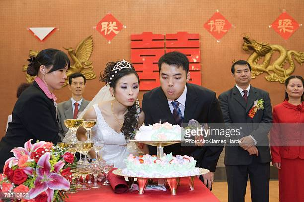 Newlyweds blowing out candle on wedding cake together