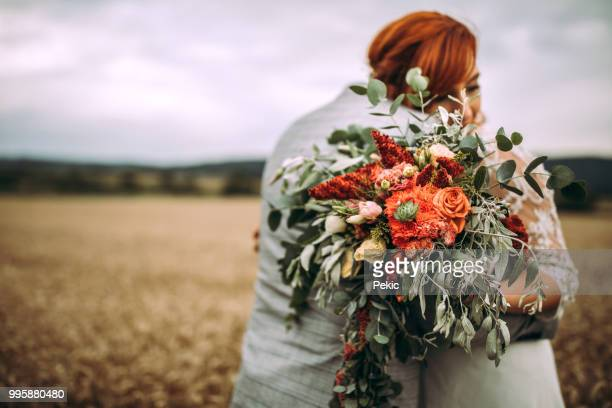 newlyweds celebrating their wedding day in rural scenery - bouquet foto e immagini stock