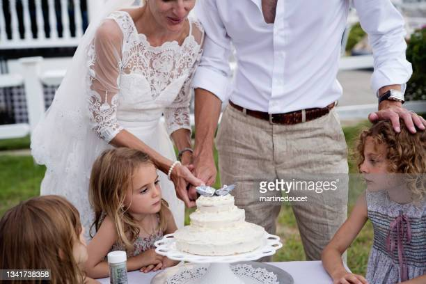 """newlyweds cutting the cake at small wedding celebrations. - """"martine doucet"""" or martinedoucet stock pictures, royalty-free photos & images"""