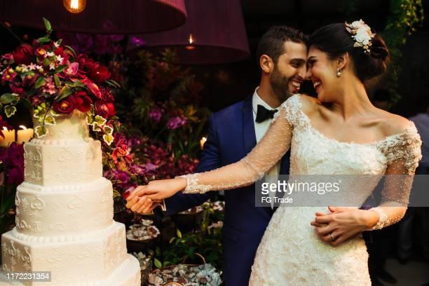 newlyweds cutting wedding cake - wedding reception stock pictures, royalty-free photos & images