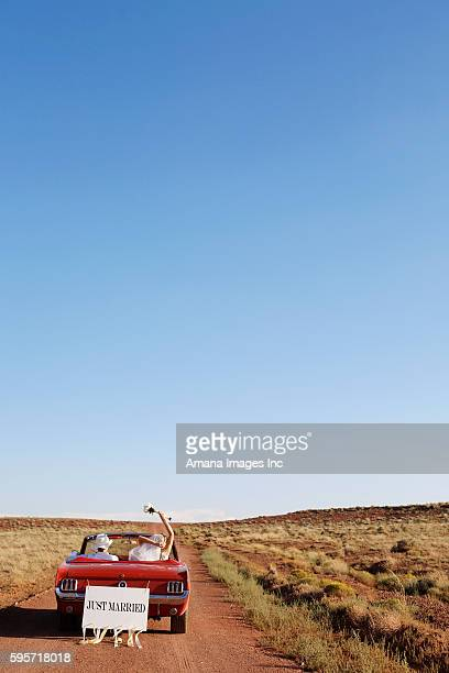 Newlyweds Driving Convertible Through Desert