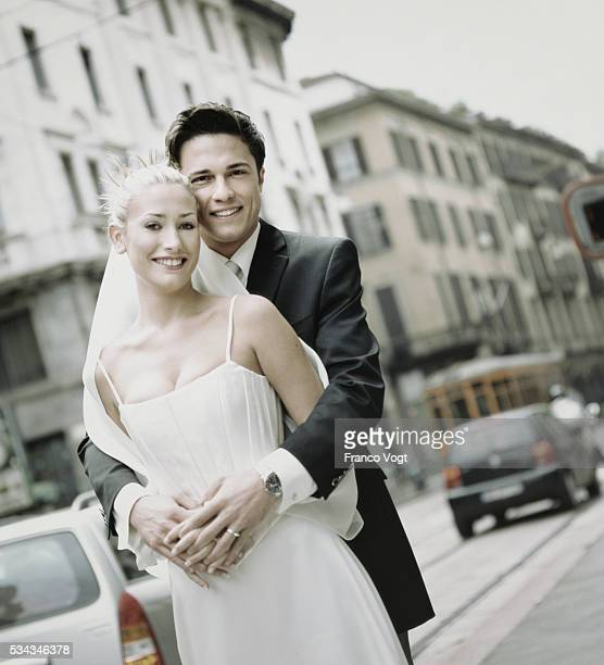 newlyweds embracing on city sidewalk - flat chested woman stock photos and pictures