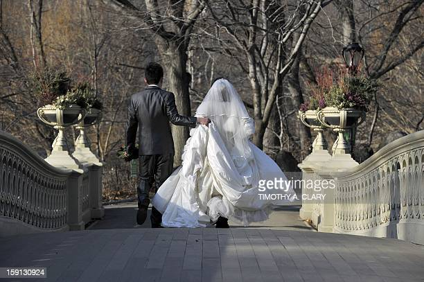 Newlyweds getting ready to pose for wedding photos cross the Bow Bridge in Central Park as New Yorkers and tourists take advantage of the unusually...