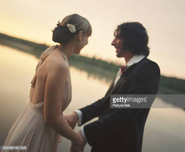 Newlyweds holding hands by lake, side view, dusk (soft focus)