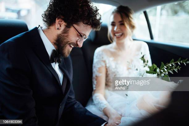 newlyweds holding hands in the backseat - groom human role stock pictures, royalty-free photos & images