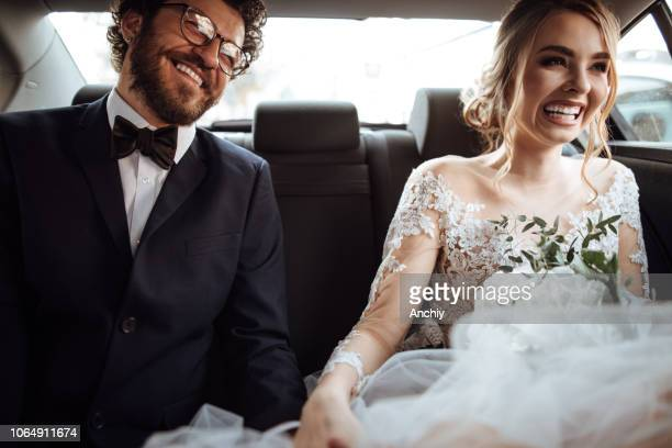 newlyweds holding hands in the backseat - wedding stock pictures, royalty-free photos & images