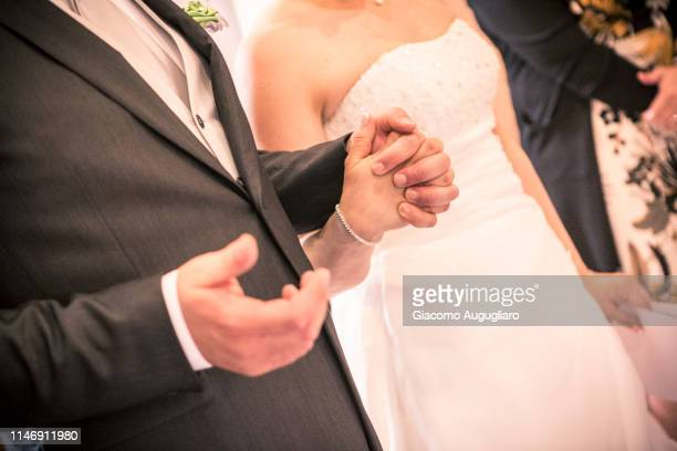 Newlyweds holding their hands during a wedding ceremony. Italy