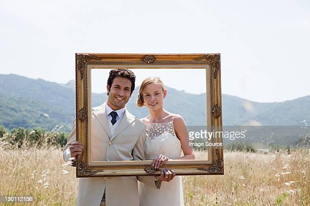 paar hält vintage bilderrahmen - hochzeit fotos stock-fotos und bilder