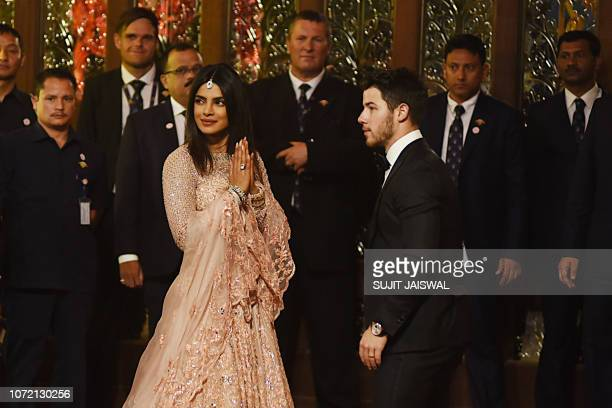 Newlyweds Indian Bollywood actress Priyanka Chopra and US musician Nick Jonas attend the wedding ceremony of Indian businesswoman Isha Ambani with...