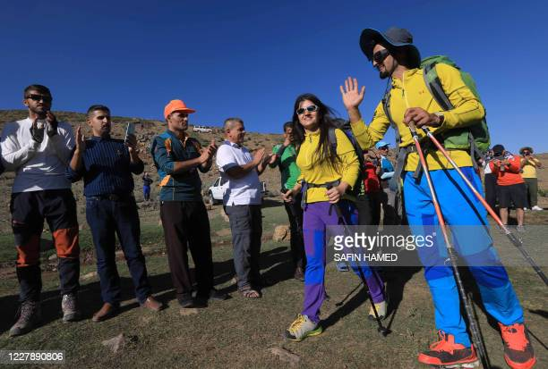 Newlyweds Iraqi Kurds Salar Chomany and Soma Mohammed walk together during a trekking ceremony at Mount Halgurd, in Iraq's autotomous Kurdistan...