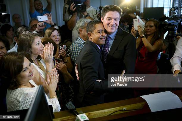 Newlyweds Jeff Delmay and Todd Delmay hug as Karla Arguello and Catherina Pareto who also were married look on during a marriage ceremony in the...