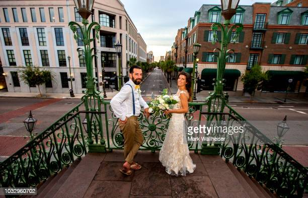 Newlyweds Kathryn and Anthony Palmisano stand on the steps of the Charleston City Market in a deserted downtown September 13 2018 in Charleston South...