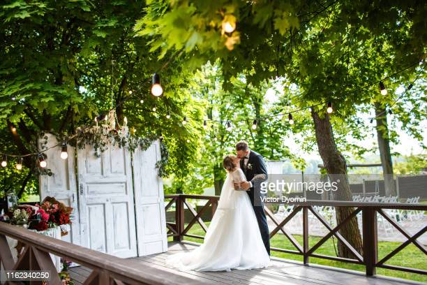 newlyweds kiss on reception area - ceremony stock pictures, royalty-free photos & images