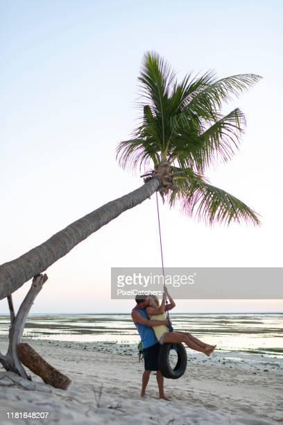 nygifta kyss på tropiska ön däck swing hängande från lone palm tree - partire bildbanksfoton och bilder