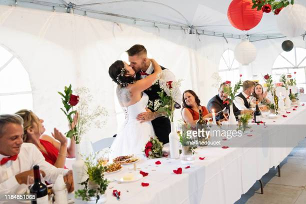 """newlyweds kissing at the table of honour at wedding reception. - """"martine doucet"""" or martinedoucet stock pictures, royalty-free photos & images"""