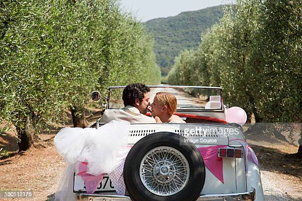 Newlyweds kissing in classic car
