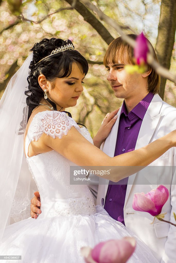Newlyweds on nature background with blossoming magnolias : Stock Photo