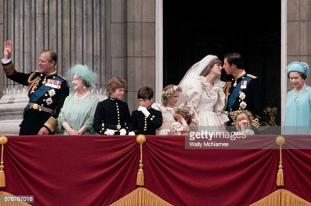 Newlyweds Princess Diana and Prince Charles kiss on the balcony at Buckingham Palace just after their wedding, surrounded by the royal family and...