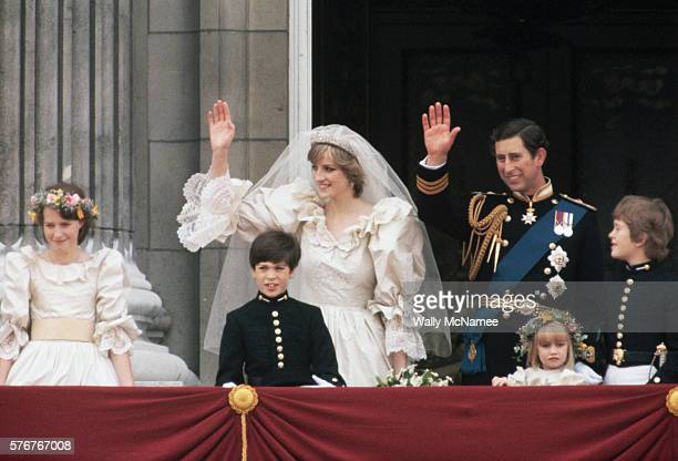 Newlyweds Princess Diana and Prince Charles wave to onlookers from the balcony at Buckingham Palace just after their wedding attended by young...