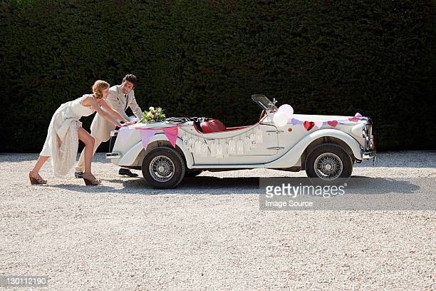 Newlyweds pushing broken down vintage car