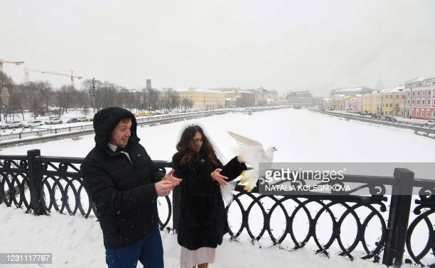 Newlyweds release a dove on a bridge in downtown Moscow during a snowfall on February 12 days before Valentine's Day.