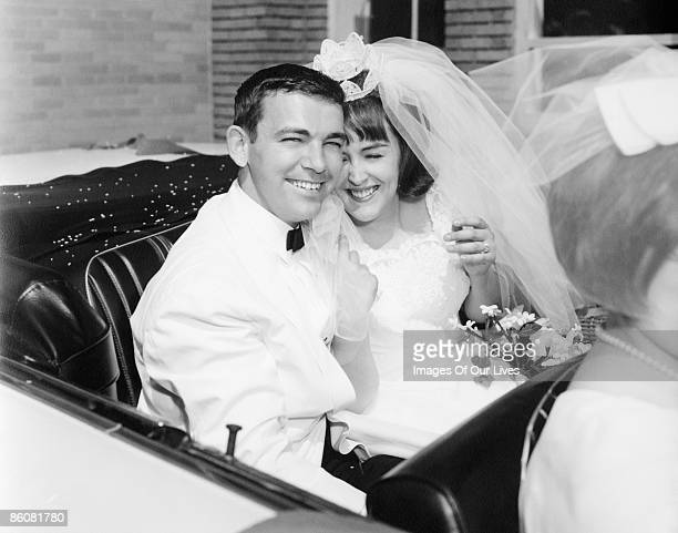 Newlyweds smiling in convertible