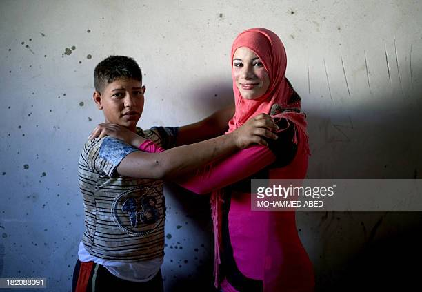 Newlyweds Tala Soboh and her 15yearold husband Ahmed Soboh pose for a photograph at their home four days after their wedding in the northern Gaza...