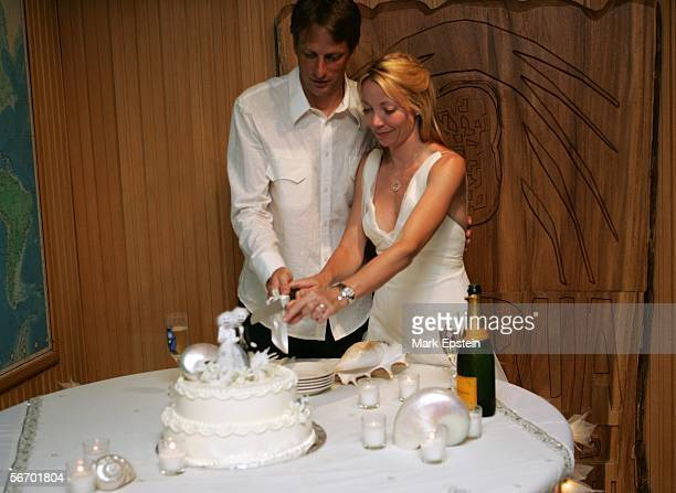Newlyweds Tony Hawk and Lhotse Merriam cut a slice of cake at their wedding reception January 12 2006 on the Island of Tavarua in Fiji