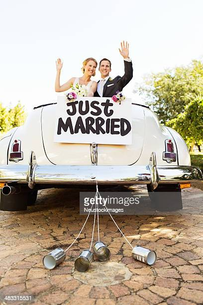 newlyweds waving in convertible car with cans attached to it - newlywed stock pictures, royalty-free photos & images