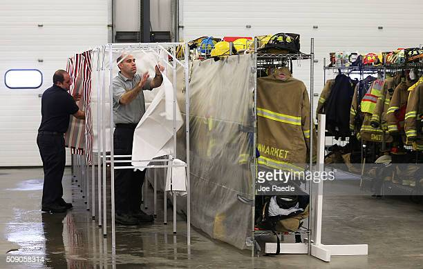 Newmarket Fire and Rescue firefighter, Gary Lemoine and Lt. Andrew Carroll set up a polling station in preparation for tomorrow's primary voters on...