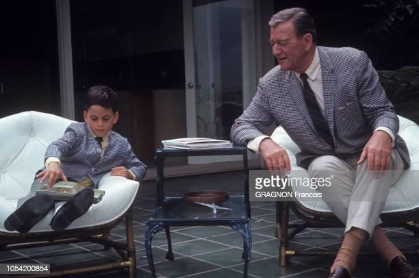 Newport Beach Californie Juin 1967 John WAYNE avec sa femme Pilar et leurs deux enfants Ethan et Marisa Ici l'acteur américain et son fils assis sur...