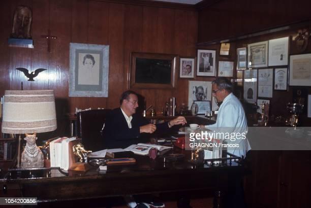 Newport Beach Californie Juin 1967 John WAYNE avec sa femme Pilar et leurs deux enfants Ethan et Marisa Ici l'acteur américain assis à son bureau se...