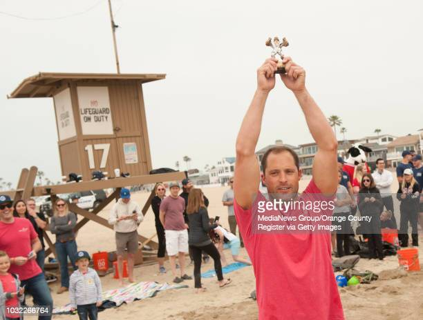 Newport Beach lifeguard Gary Conwell celebrates his team's victory after an obstacle course and sand castle competition between police firefighters...