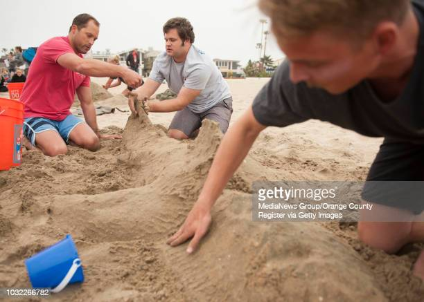 Newport Beach lifeguards Gary Conwell Tim Thomas and Alex Brandt from left work on their shark sculpture during an obstacle course and sand castle...