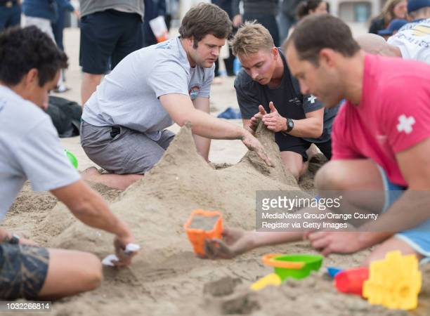 Newport Beach lifeguards Tim Thomas center left and Alex Brandt fine tune a fin on their shark sculpture during an obstacle course and sand castle...