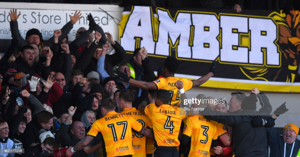 Newport County player Shawn McCoulsky (c) celebrates his winning goal with fans and team mates during The Emirates FA Cup Third Round match between Newport County and Leeds United at Rodney Parade on January 7, 2018 in Newport, Wales.
