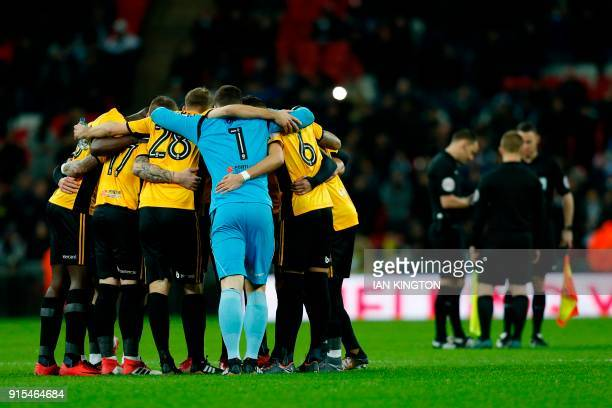 Newport County players form a huddle as match officials chat aheda of the English FA Cup fourth round replay football match between Tottenham Hotspur...