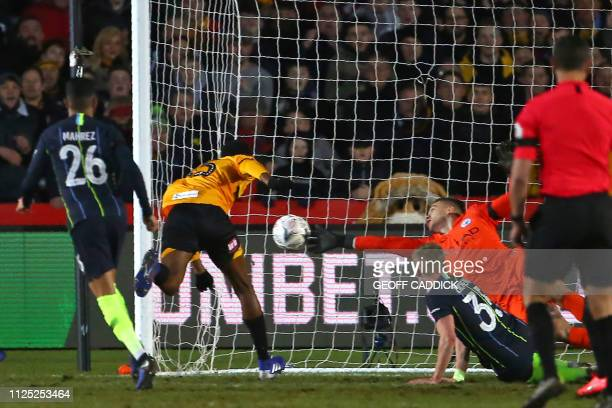 Newport County's English midfielder Tyreeq Bakinson has this header saved by Manchester City's Brazilian goalkeeper Ederson during the English FA Cup...