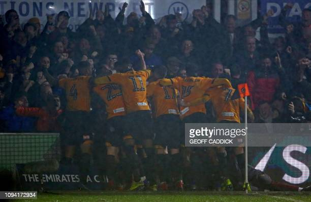 Newport County's Irish striker Padraig Amond is mobbed by teammates after scoring his team's second goal during the English FA Cup fourth round...