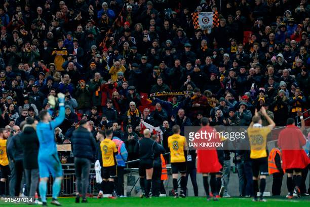 Newport County's players applaud their travelling support on the pitch after the English FA Cup fourth round replay football match between Tottenham...
