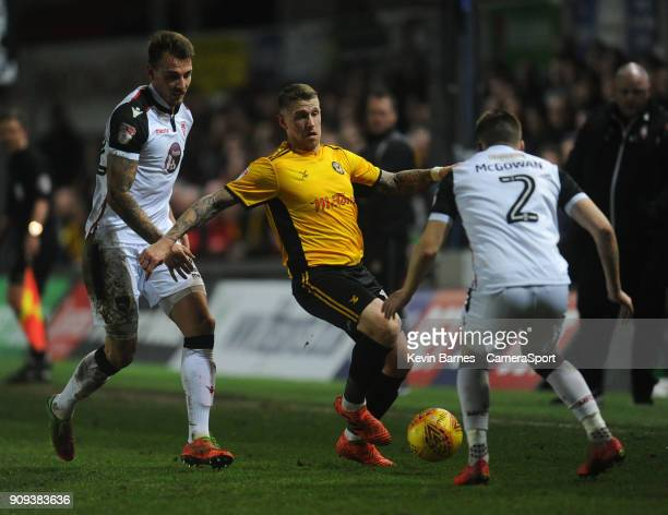 Newport County's Scot Bennett under pressure from Morecambe's Max Muller and Aaron McGowan during the Sky Bet League Two match between Newport County...