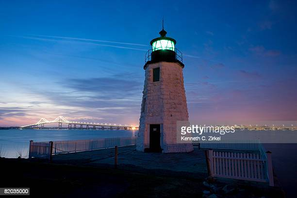 Newport Harbor Light, aka Goat Island Lighthouse, Newport, RI, at sunset, with Pell Bridge behind it.