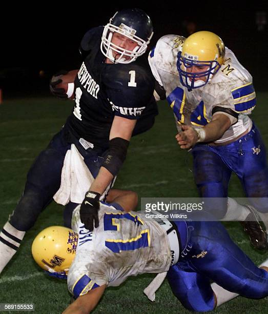 Newport Harbor player @@ 1 Chris Manderino is tackled by La Mirada players @@ 17 Junior Vaca and @@ 44 Ricky Lepe in the third quarter in the...