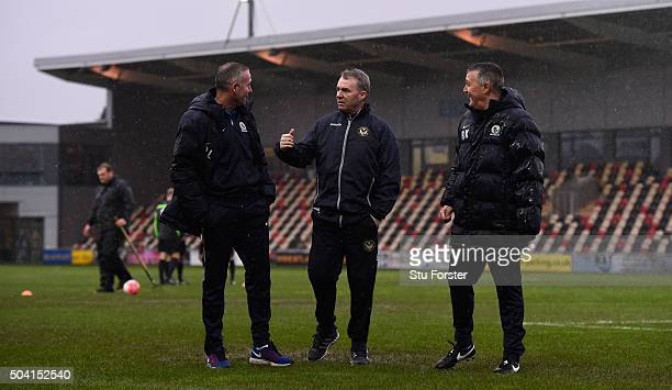 Newport manager John Sheridan discusses the possibilities of play on a waterlogged pitch with Blackburn manager Paul Lambert and coach Mike Kelly...